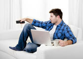 Relaxed man using Computer at home switching tv on — Stock Photo