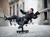 business man rolling downhill on chair with computer and tablet — Stock Photo