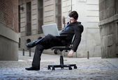 Tired Business Man sitting on Office Chair on Street sleeping — Zdjęcie stockowe