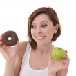 Young sport Woman with Apple and Chocolate Donut in Hands in healthy versus junk food dessert choice isolated on White background — Stock Photo