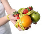 Woman hands with fruit  bond with measure tape slave to diet — Stock Photo