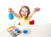 little girl painting dyed egg for Easter celebration  — Стоковое фото