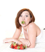 Young Attractive woman eating a bowl of strawberries in bed — Stock Photo