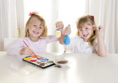 happy blonded girls painting a easter eggs white window  — Stock Photo