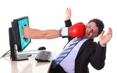 Business man with computer hit by boxing glove in stress concept — Stock Photo