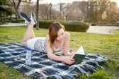 Pretty red haired woman reading a book in the park — Stock Photo