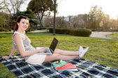 Pretty red haired woman working on laptop in a park — Stock Photo