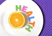 Halved fresh and healthy Orange Fruit stillife and health word on plate  — Stock Photo