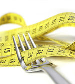 Silver fork wrapped in measure tape in diet and overweight concept  — Stock Photo