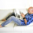 Young attractive man couching with computer and phone — Stock Photo #44966411