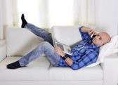 Young attractive man couching with computer and phone — Stock Photo