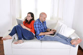 Antisocial latin couple while on laptop and tablet — Stock Photo