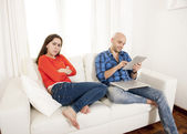 Latin girlfriend not happy with boyfriend playing on laptop — Stock Photo
