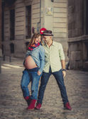 Happy young cool  latin couple together outdoors with pregnant woman showing belly — Stock Photo