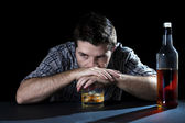 Drunk alcoholic man with whiskey glass and bottle in alcohol addiction and alcoholism concept — Stock Photo