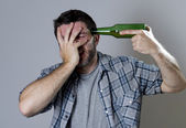 Crazy man holding beer bottle as a gun with handgun pointing to his head — Stock Photo