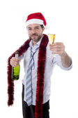 Businessman drinking champagne wearing a santa hat on white background — Stock Photo