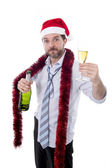 Drunk businessman drinking champagne wearing a santa hat on white background — Stock Photo
