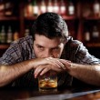 Alcoholic drunk man thoughtful on alcohol addiction at bar of pub — Stock Photo #50025197