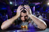Alcoholic drunk man thoughtful on alcohol addiction at disco nightclub — Photo