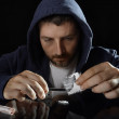 Young drug addict man on hood alone ready preparing cocaine lines — Stock Photo #50211003