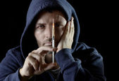 Sick drug addict man wearing hood holding heroin or cocaine syringe — Stockfoto