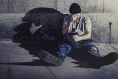 Young man sitting sick on street ground with shadow on concrete wall feeling miserable and sad in urban scene in depression — Stock Photo