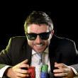 Happy young attractive man grabbing poker chips after winning bet gambling — Stock Photo #50533793