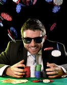 Happy young attractive man grabbing poker chips after winning bet gambling — Stock Photo