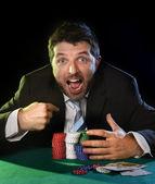 Homem feliz pegar fichas de poker, depois de vencer o jogo aposta — Fotografia Stock