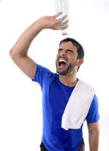 Young attractive and athletic sport man exhausted pouring water on his face — Stock Photo