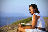 Attractive 40s mature woman reading and looking at horizon pensive — Photo