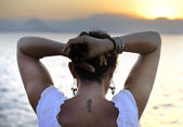 Woman with back seahorse tattoo standing alone looking at sea horizon — Stock Photo