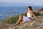 Attractive 40s mature woman sitting alone on the beach thinking and looking at horizon pensive — Stockfoto