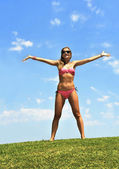 Happy young woman in bikini opening arms to the air in summer sky — Stock Photo