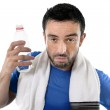 Athletic sport man  holding water bottle wiping out sweat after  — Stock Photo #51412381
