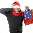 Young stressed man wearing santa hat holding red shopping bags — Stock Photo #51526531