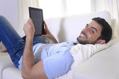 Young happy attractive man using digital pad or tablet sitting on couch — Stock Photo