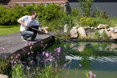 Man cleanse his garden pond — Stock Photo