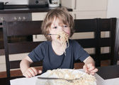 Boy has mouth full of pasta in kitchen — Stock Photo