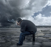 Depressed young man sitting on a chair, smoking a cigarette — Stock Photo