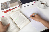 Student learning, taking notes, on a desk with books — Stock Photo