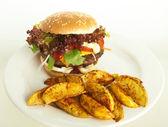 Cheeseburger with potato wedges — Stock Photo