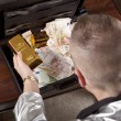 Man with suitcase full of money and gold — Stock Photo