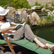 Woman reads at the pond — Stock Photo