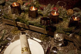 Christmas laid table in the candlelight — Stok fotoğraf