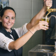 Young waitress serving draft beer — Stock Photo