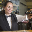 Waitress serving red wine — Stock Photo