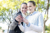 Two women using a smartphone — Stock Photo