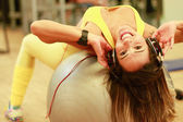Woman listening music in ball fitness — ストック写真